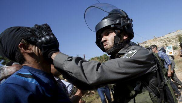 Un policía israelí golpea a un palestino en Cisjordania - Sputnik Mundo