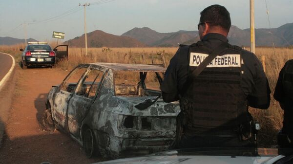 Federal police stand next to a bullet riddled and burned car after a criminal gang ambushed a police convoy near the town of Soyatlan, near Puerto Vallarta - Sputnik Mundo