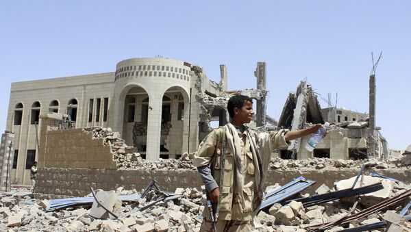 A Houthi militant stands in front of a court building, which was damaged in a Saudi-led air strike in Saada May 31 - Sputnik Mundo