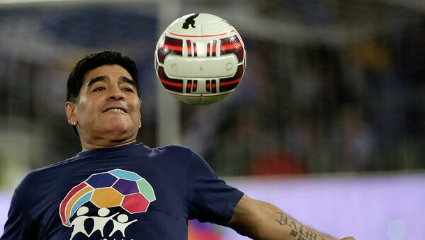 Argentine soccer legend Diego Armando Maradona watches the ball as he warms up prior to the start of an inter-religious match for peace, supported by Pope Francis to promote the dialogue and peace among different religions, at Rome's Olympic Stadium, Monday, Sept. 1, 2014.  - Sputnik Mundo