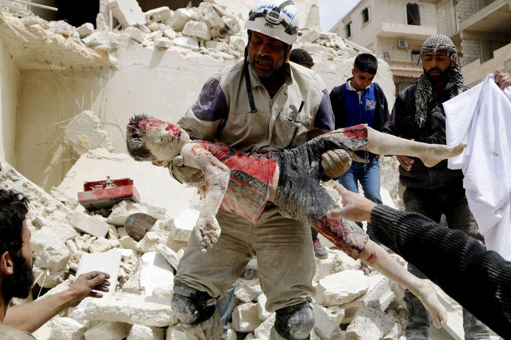 Un soldado de las tropas de Defensa Civil llevando el cuerpo de un niño muerto