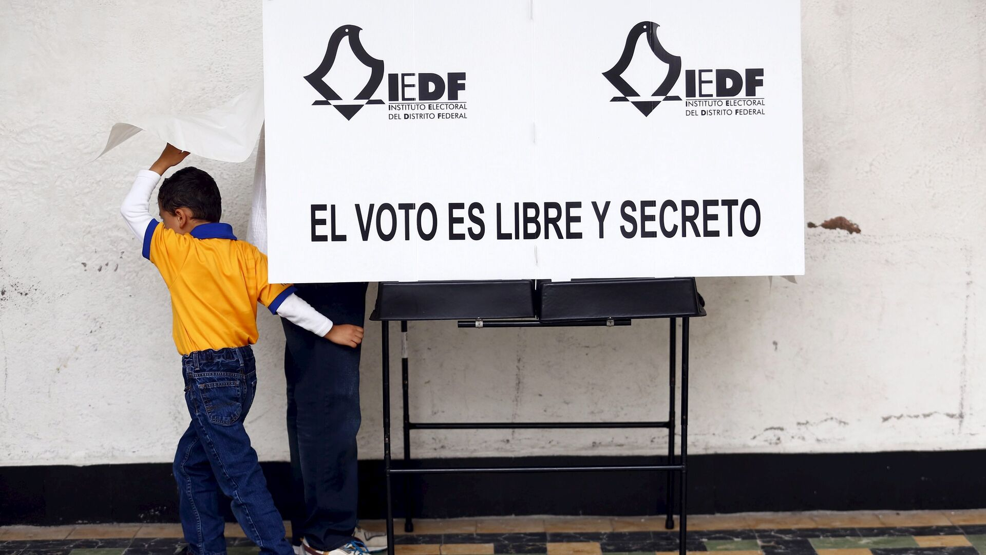 A man casts his ballot next to his son during midterm elections in Mexico City, June 7, 2015.  - Sputnik Mundo, 1920, 05.06.2021
