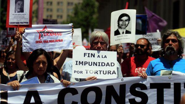 Manifestantes mantienen carteles con fotos de víctimas de la dictadura de Augusto Pinochet - Sputnik Mundo