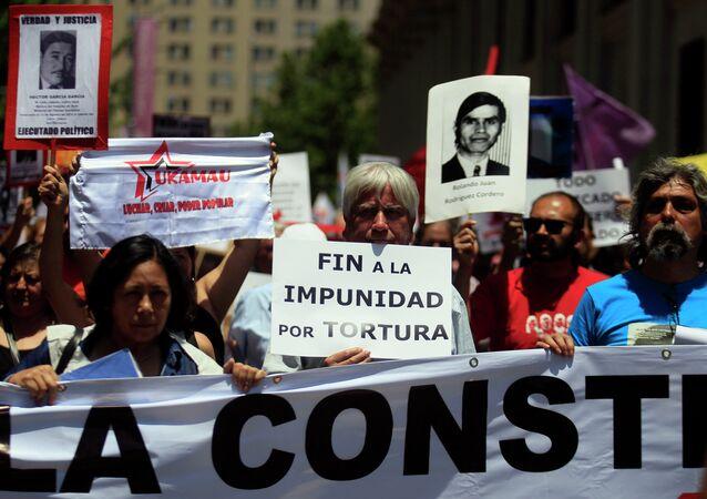 Manifestantes mantienen carteles con fotos de víctimas de la dictadura de Augusto Pinochet