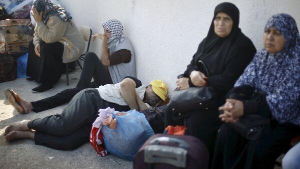 Palestinos esperan permisos de viaje para cruzar a Egipto, en la ciudad fronteriza de Rafah - Sputnik Mundo