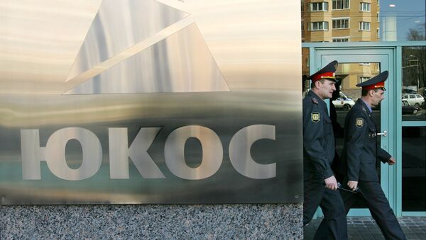 Two policemen pass by the Yukos logo in Moscow during the auction of a package of assets of the stricken Yukos oil giant 27 March 2007. - Sputnik Mundo