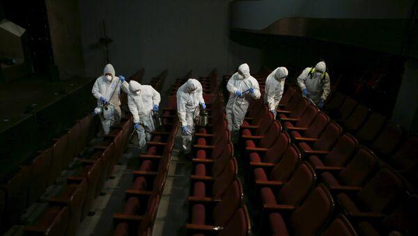 Empleados de un servicio de desinfección en un teatro de Seúl - Sputnik Mundo