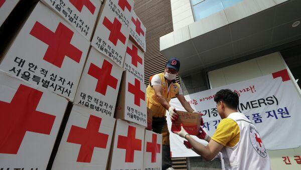 Los miembros de la Cruz Roja de Corea del Sur descargan  un camión con ayuda para las personas que se sospecha de la infección - Sputnik Mundo