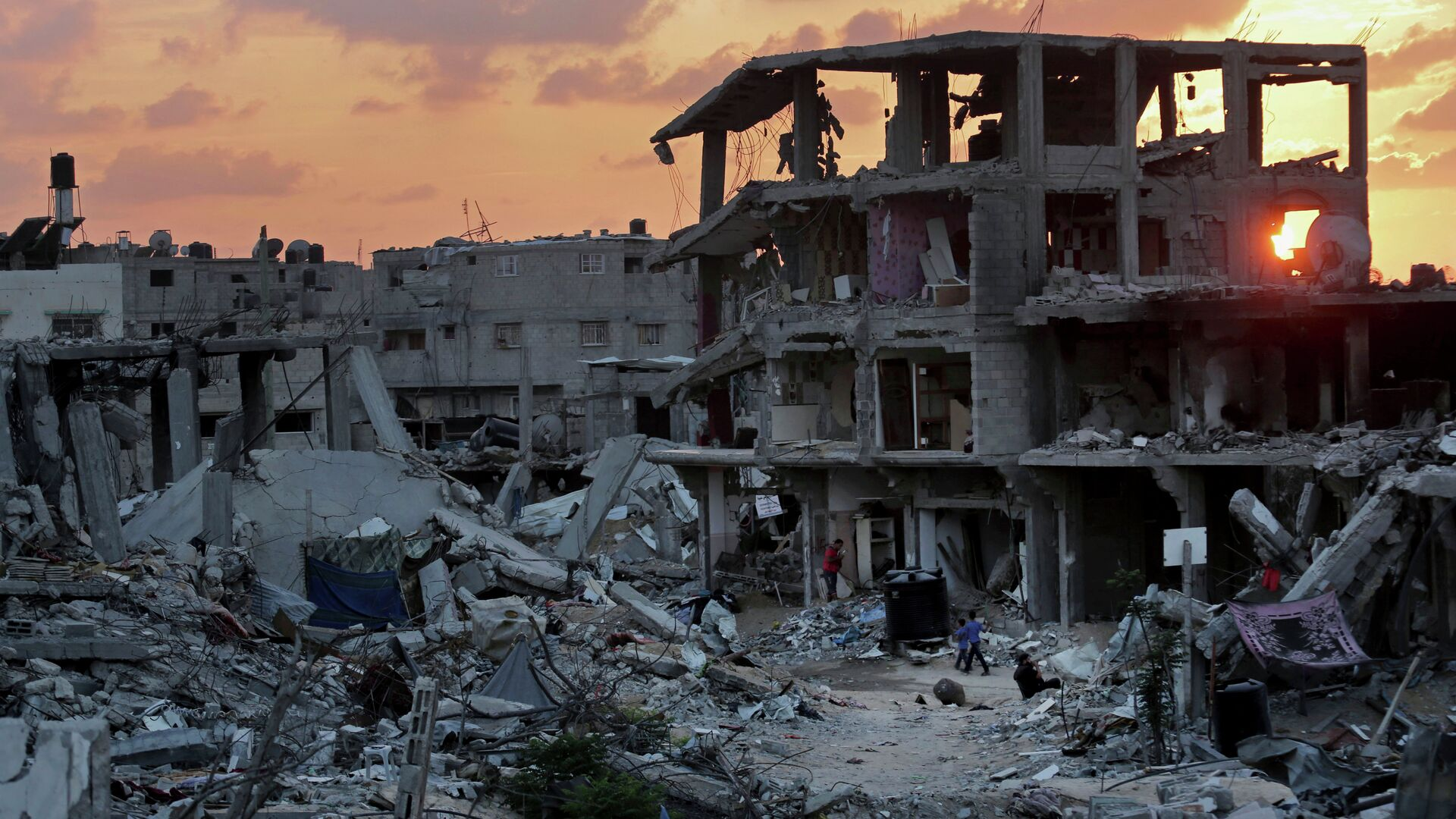 Palestinians walk during the sunset between the rubble of their destroyed building in Shijaiyah neighborhood of Gaza City in the northern Gaza Strip, Sunday, Oct. 12, 2014 - Sputnik Mundo, 1920, 25.07.2021