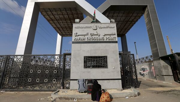 A Palestinian woman sits in front of the gate of Rafah border crossing as she waits for a travel permit to cross into Egypt, in Rafah in the southern Gaza Strip June 14, 2015. - Sputnik Mundo