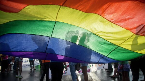 Members of the LGBT movement hold a gay pride flag as they attend a march to mark the International Day Against Homophobia in Managua, Nicaragua, Sunday, May 17, 2015. - Sputnik Mundo