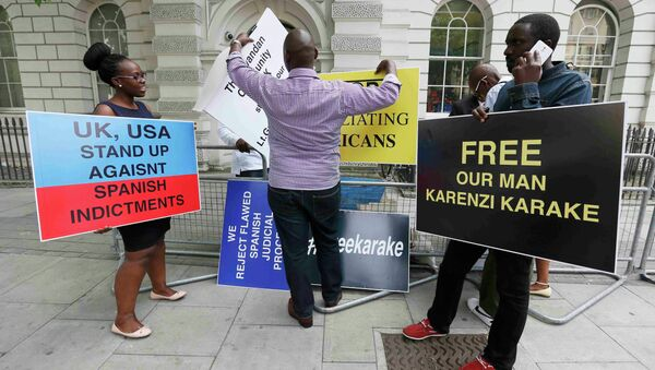 Manifestantes sostienen carteles exigiendo la liberación de jefe de inteligencia de Ruanda Karenzi Karake en Londres - Sputnik Mundo