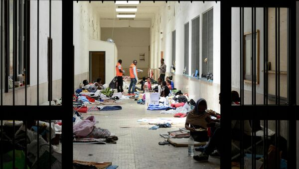 Migrants are seen on the floors in a hallway at the Vintimiglia train station in Italy, on World Refugee Day, June 20, 2015. - Sputnik Mundo
