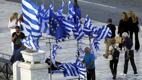 A street vendor sells Greek and EU flags before an upcoming demonstration by Greeks calling on the government to clinch a deal with its international creditors and secure Greece's future in the Eurozone in Athens, Greece, June 22, 2015 - Sputnik Mundo