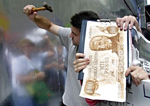 Los argentinos rompen una pared de metal del banco en Buenos Aires en protesta por el bloqueo de sus ahorros