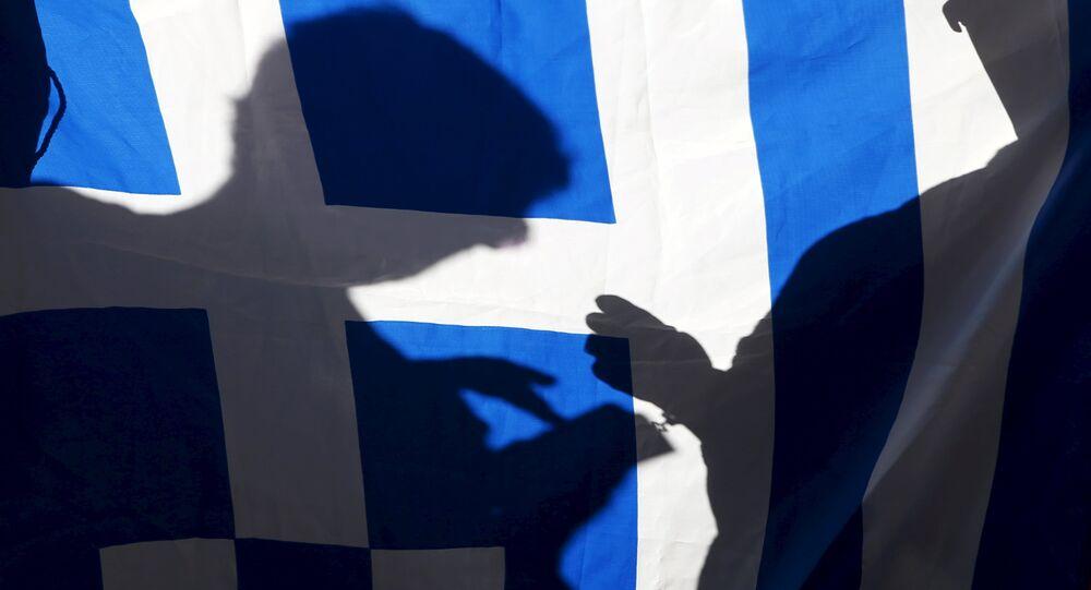 La silueta de un hombre con su teléfono en una bandera de Grecia
