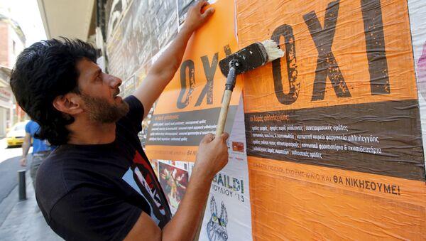 Un hombre pega un póster con la palabra griega NO en Atenas - Sputnik Mundo