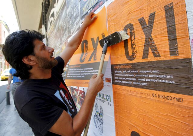 Un hombre pega un póster con la palabra griega NO en Atenas