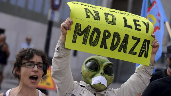 A man wearing a mask with a tape over the mouth holds up a sign during a protest against the Spanish government's new security law in Gijon, northern Spain, June 30, 2015. - Sputnik Mundo