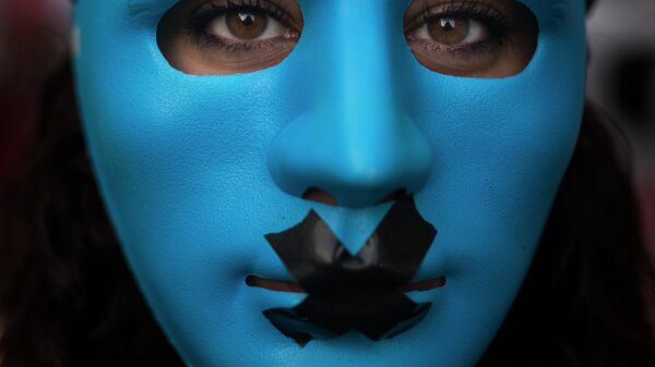 A protestor wears a mask with a gag as she marches against the Public Security Law in Madrid, Spain, Tuesday, June 30, 2015. - Sputnik Mundo