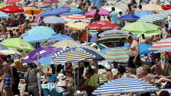 Gente pasa el tiempo en la playa cerca de Barcelona durante la ola de calor - Sputnik Mundo