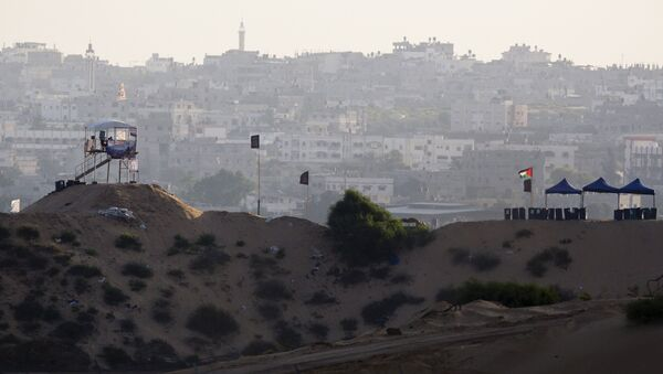 A Palestinian flag flutters near a watch tower in northern Gaza near the border with Israel (bottom) July 6, 2015 - Sputnik Mundo