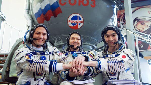 Tripulación de EEI-44/45 al lado de cohete Soyuz - Sputnik Mundo