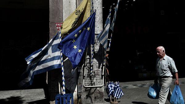 Un hombre camina delante de las banderas de UE y Grecia en el centro de Atenas. 13 de julio de 2015 - Sputnik Mundo