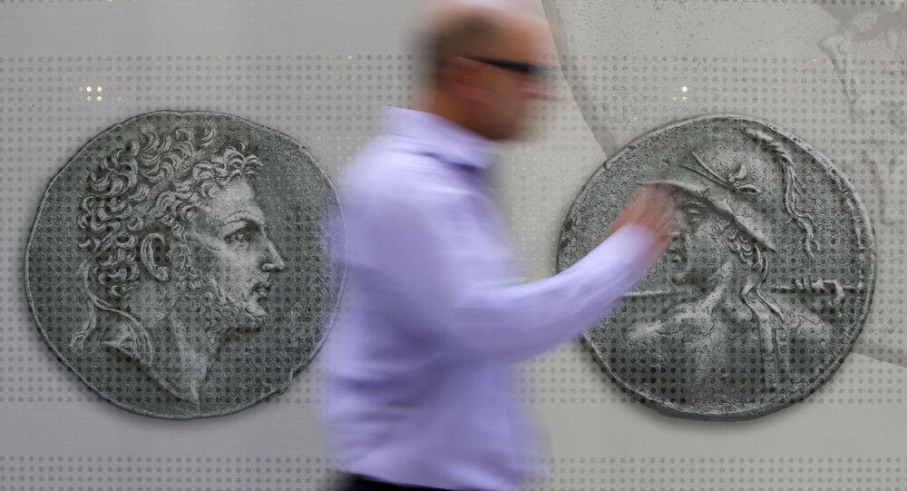 Un hombre camina delante de las monedas en el centro de Atenas. 13 de julio de 2015