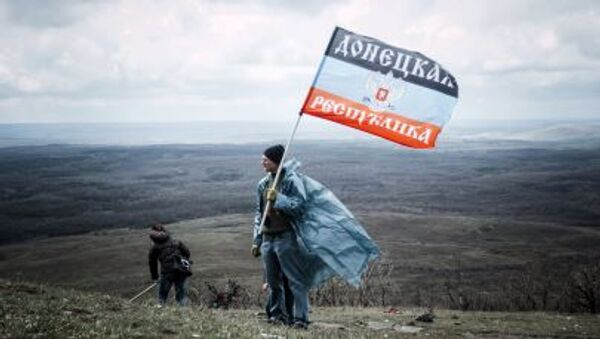 Hombre con la bandera de la RPD cerca el monumento de Saur Moguila en Donetsk, Ucrania - Sputnik Mundo