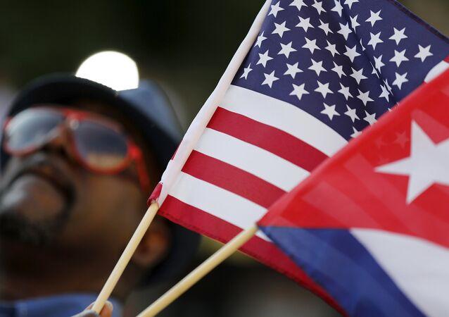 Un hombre sostiene las banderas de Estados Unidos y Cuba momentos antes de que la bandera cubana fuera hizada en la Embajada de Cuba en Washington el 20 de julio de 2015.