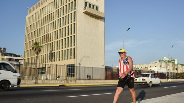 A man wearing a sleeveless shirt with the US flag walks along the Malecon seafront near the US Embassy, on July 20, 2015. T - Sputnik Mundo
