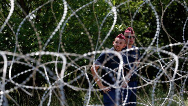 Policías húngaros guardan una valla contra migrantes - Sputnik Mundo