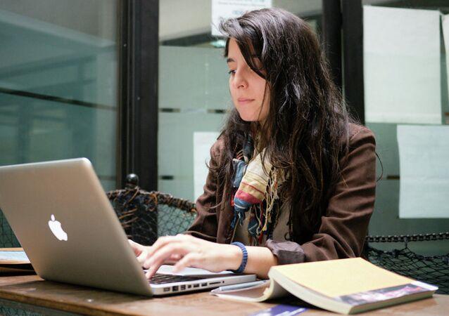 Una joven delante del ordenador portátil