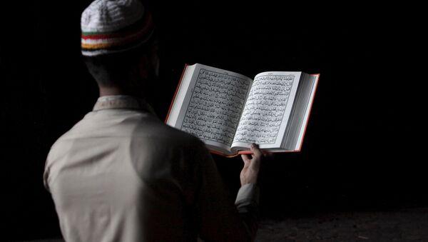 Hombre lee el Corán - Sputnik Mundo