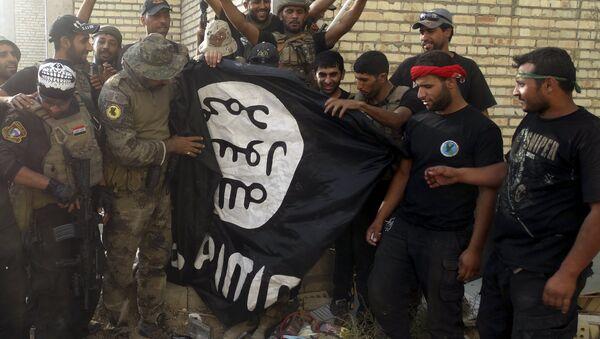 Fuerzas de seguridad de Irak con una bandera de Estado Islámico en provincia de Anbar, Irak, el 26 de julio, 2015 - Sputnik Mundo