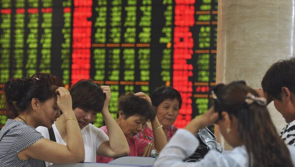Investors react as they look at computer screens showing stock information at a brokerage house in Fuyang, Anhui province, China - Sputnik Mundo