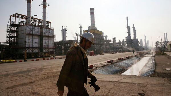 Trabajador petrolero iraní camina cerca una refinería de petróleo en Teherán, Irán - Sputnik Mundo