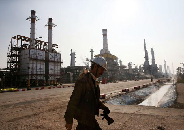 Trabajador petrolero iraní camina cerca una refinería de petróleo en Teherán, Irán