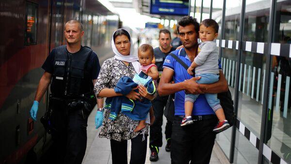 Policía acompaña una familia de refugiados afganos en Rosenheim, Alemania, el 28 de julio, 2015 - Sputnik Mundo
