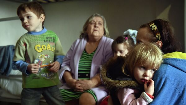 A Refugee family from a city in the Donetsk region controlled by pro-Russia separatists sit together in a center for refugees in the eastern Ukrainian city of Slavyansk, which is controlled by Ukrainian forces on March 12, 2015. - Sputnik Mundo