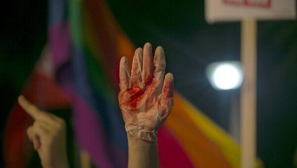 Manifestante levanta el mano en un guante cubierto de sangre falsa durante protestas contra violencia contra comunidad gay en Israel - Sputnik Mundo