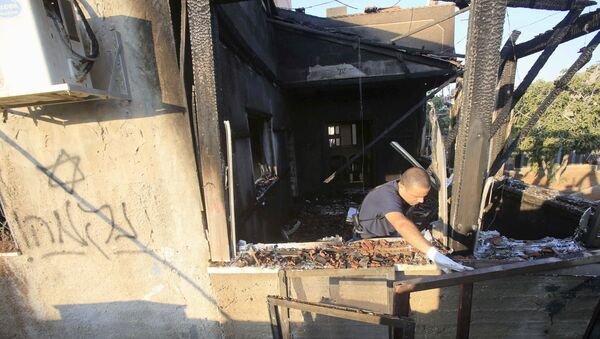 An Israeli police officer inspects a house that was badly damaged from a suspected attack by Jewish extremists on two houses at Kafr Duma village near the West Bank city of Nablus - Sputnik Mundo