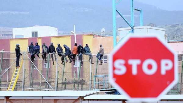 Would-be immigrants sit atop a border fence separating Morocco from the north African Spanish enclave of Melilla in the first attempt to jump in on February 19, 2015 - Sputnik Mundo