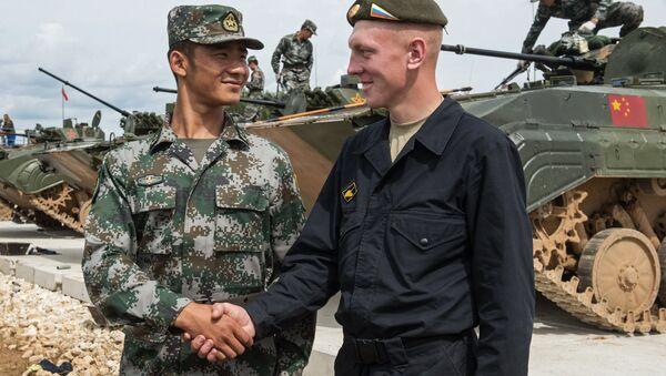 Soldado chino y soldado ruso se dan un apretón de manos durante Juegos Militares de Rusia - Sputnik Mundo