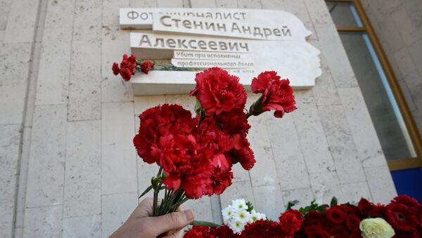 Flores en la placa conmemorativa en honor al periodista Andréi Stenin - Sputnik Mundo