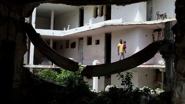 Un padre sostiene a su hija fuera de su habitación en Puerto Príncipe - Sputnik Mundo