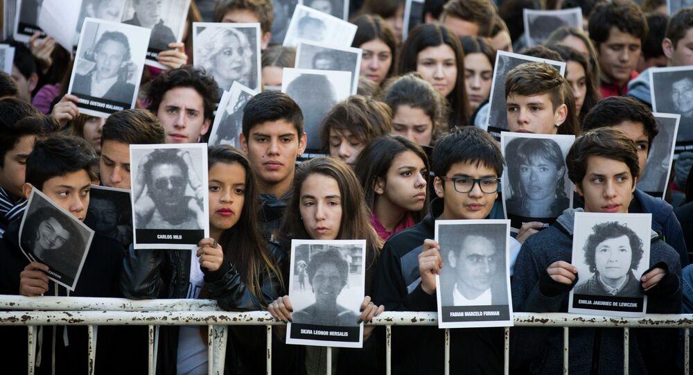 Manifestantes con fotos de victimas de ataque a la AMIA durante un mitin en conmemoración de 21º aniversario de atentado en Buenos Aires, Argentina