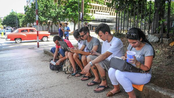 Cubans use their mobile devices to connect to internet via wi-fi in a street of Havana, on July 2, 2015 - Sputnik Mundo