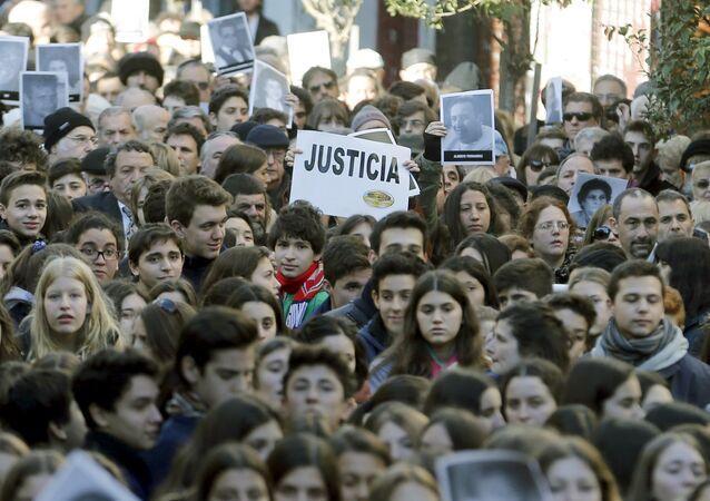 Manifestantes con fotos de victimas de ataque a la AMIA durante un mitin en conmemoración de 21º aniversario de atentado en Buenos Aires, Argentina (archivo)